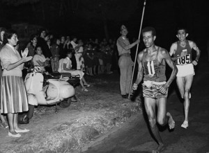Abebe Bikila of Ethiopia, running barefoot, draws away from Abdesselem Rhadi of Morocco near the finish of the marathon at the 1960 Rome Olympics. He went on to win with a new Olympic record time of 2 hours 15 minutes 16 seconds. (Photo by Central Press/Getty Images)